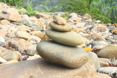 Stones pyramid near small river symbolizing zen Stock Photos
