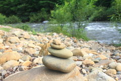 Stones pyramid near small river symbolizing zen Royalty Free Stock Photo