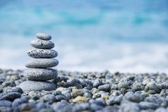 Stones pyramid on pebble beach symbolizing spa concept with blur sea background Royalty Free Stock Images