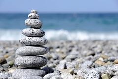 Stones pyramid on pebble beach symbolizing spa concept with blur sea background Royalty Free Stock Image