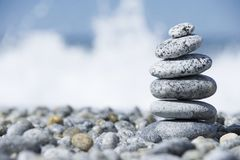 Stones pyramid on pebble beach symbolizing spa concept with blur sea background Royalty Free Stock Photography