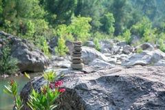 Stones pyramid on rock symbolizing stability, zen, harmony. Stock Images
