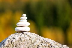 Stones pyramid on rock symbolizing zen, harmony, balance, with f. Orest in the background royalty free stock photo