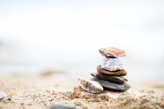 Stones pyramid on sand. Sea in the background Stock Photography