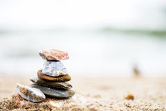 Stones pyramid on sand. Sea in the background Royalty Free Stock Image