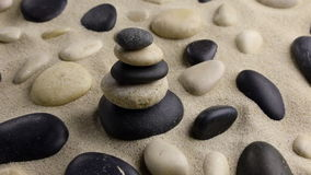 Stones pyramid on sand standing among the rocks stock footage