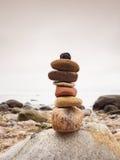 Stones pyramid symbolizing zen, harmony, balance pebbles. Ocean in background Royalty Free Stock Photo