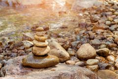 Stones pyramid at waterfall. Selective focus Royalty Free Stock Photo