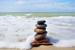 Stones in pyramid and wave on sand beach Stock Photography