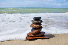 Stones in pyramid and wave on sand beach Royalty Free Stock Image