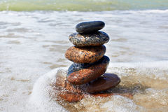 Stones in pyramid and wave on sand beach Royalty Free Stock Images