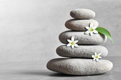 Stones pyramid with a white flower on grey background and leaf Stock Image