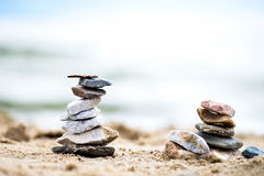Stones Pyramids on Sand. Sea in the background Royalty Free Stock Image
