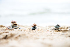 Stones Pyramids on Sand. Sea in the background Royalty Free Stock Images