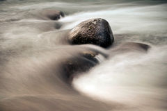 Stones among rapid water flow Royalty Free Stock Images
