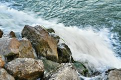 Stones among rapid water flow Royalty Free Stock Image