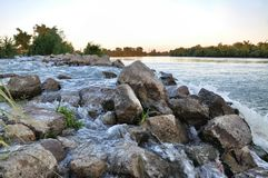 Stones among rapid water flow Royalty Free Stock Photos