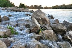 Stones among rapid water flow Royalty Free Stock Photography