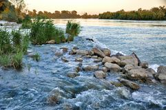 Stones among rapid water flow Royalty Free Stock Photo