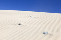 Stones in the rippled sand of Maspalomas, Canary Islands. Stock Images