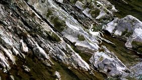 Wet old rocks with mossin water. Stones and rockes in water, wet, solid and massive. Good as background Royalty Free Stock Images