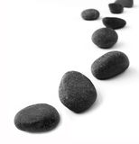 Stones in a row. A row of black pebbles placed in a row receding into distance.  Taken on clean white background with copy space Stock Photos