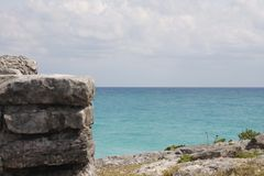 Stones of  Ruin in front of  the sea of Tulum, Mexico. Beautiful sea of Tulum, escorted by this stones of the ruins in the view, allow admire the blue turquoise royalty free stock images