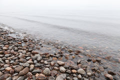Stones on Saimaa lake in foggy morning Stock Images