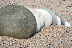 Stones in the sand. Image of 8 stones going deep in the sand Stock Photos