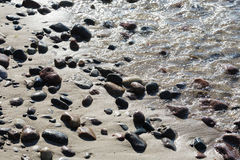 Stones on a sandy beach in Kolobrzeg Stock Photos