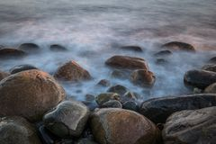 Stones at the sea beach. Wet stones at the sea beach in magic light and long exposure waves Royalty Free Stock Photography