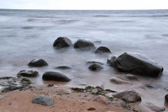 Stones in the sea. Big stones in the sea covered with mist Stock Photography