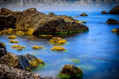 Stones, sea and green algae. Overgrown with algae and mud stones washed by sea water. A slow shutter speed. Tourism and hiking Royalty Free Stock Images