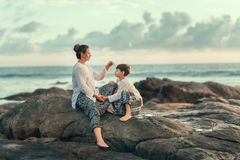On the stones of the sea, mother and son Stock Photo