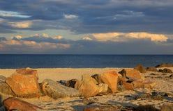 Stones on sea sandy beach in evening light stock photo