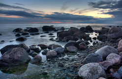 Stones in the sea after sunset Stock Photography