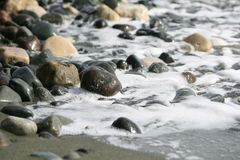 Stones and sea water on a beach royalty free stock photo