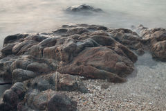 Stones by the sea. waves of the sea from long exposure Royalty Free Stock Images