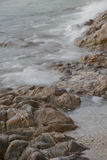 Stones by the sea. waves of the sea from long exposure Stock Photos