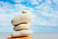 Stones on seacoast. Stack of balanced pebbles, stones against colorful blue sky Stock Images