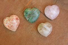 Stones in the shape of heart lie on a brown background. Heart ma. De of natural quartz stone, rhodochrosite and marble. Love talisman, spa, zen or yoga Stock Images