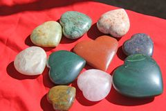 Stones in the shape of heart lie on a red background. Heart made. Of natural quartz stone, rhodochrosite, jade, aventurine and marble. Love talisman, spa, zen Royalty Free Stock Image