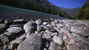 Stones on the shore of the turquoise mountain river stock video footage