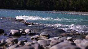 Stones on the shore of the turquoise mountain river. Glidetrack stock video