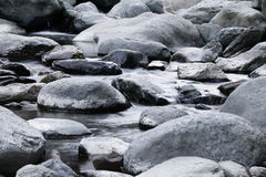 Stones. Small darck rocks splashed with Water from many small waterfalls Stock Photography
