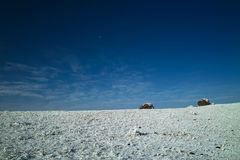 Stones on snowfield in blue sky stock photo