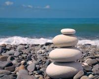 Stones stacked in balanced pile. White stones stacked in balanced pile on a pebble beach Royalty Free Stock Photos