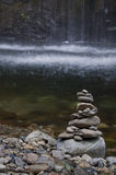 Stones stacked with soft streaming water in background. Stones stacked at the base of a river with a soft waterfall in the background royalty free stock photos