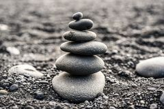 Stones stacked on top of a black beach in Iceland. Stock Photos