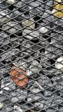 Stones in the steel cage, decorated the wall. Royalty Free Stock Photography